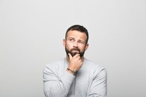 questions to ask yourself - Portrait of worried bearded young man looking up with hand on chin. Studio shot, grey background.