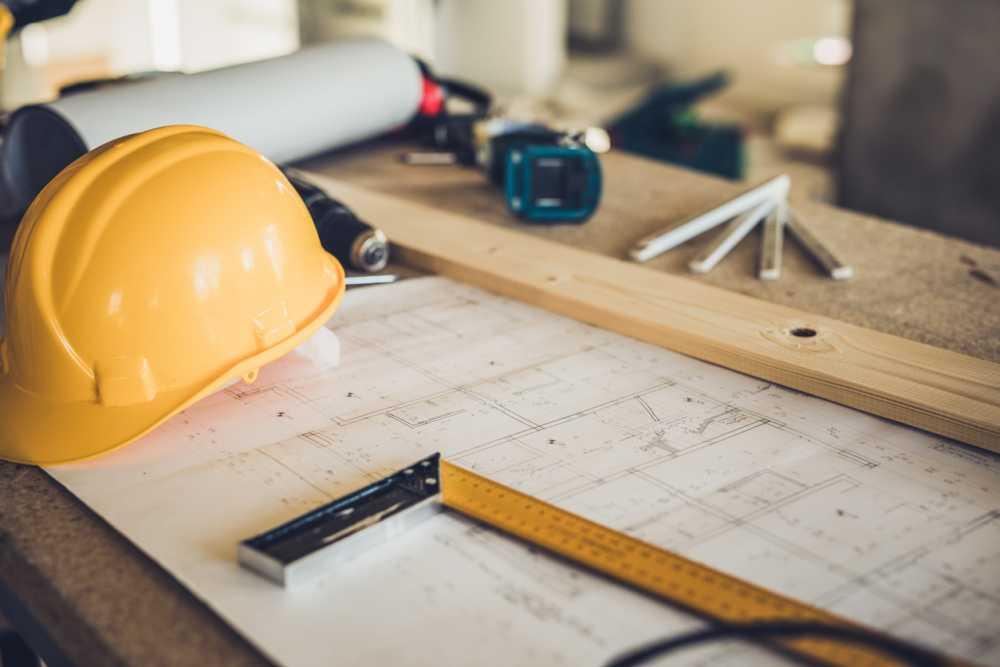 a builder helmet over floor plan papers representing construction